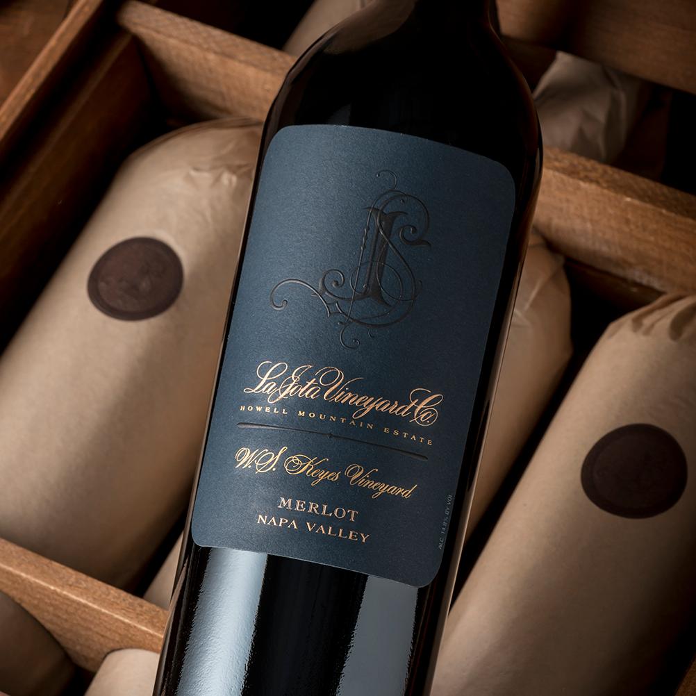La Jota WS Keyes Merlot bottle against three wrapped wine bottles in a wooden box