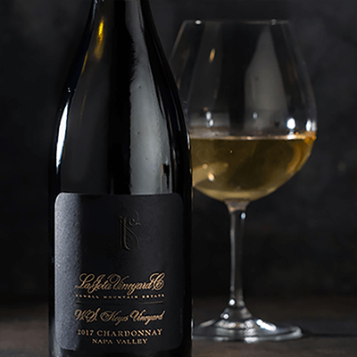 La Jota WS Keyes Chardonnay bottle shot with a wine of glass out of focus behind it on a dark background