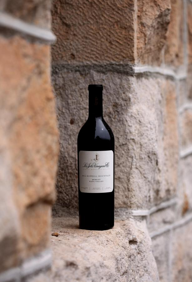 Single bottle of red wine against a stone background.