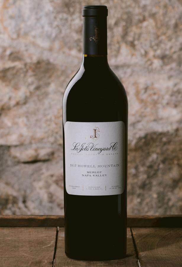 Wine bottle of La Jota Merlot againsnt a stone wall