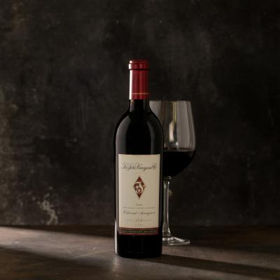 Single bottle of Cabernet with a wine glass behind the bottle against a dark gray background.