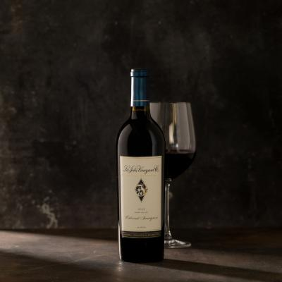 Single bottle of red wine with a wine glass behind the bottle against a dark gray background.
